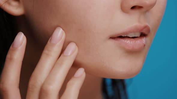 Thumbnail for Close-up of Woman Applying Moisturizer on Her Cheek and Chin on Blue Background