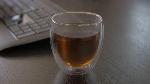 Thumbnail for Teepause nach Abschluss Job Zeitlupe 1080p FullHD Filmmaterial - Nehmen Glas Tee in der Nähe von Tastatur 1