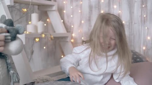 Child with Long Blond Hair Plays with Winter Themed Toys