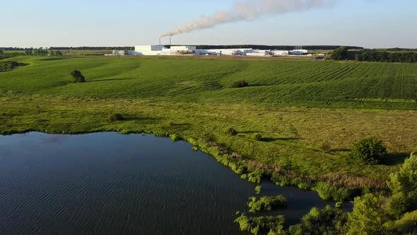 Countryside Farm With Lake. View of a factory in the middle of a green field