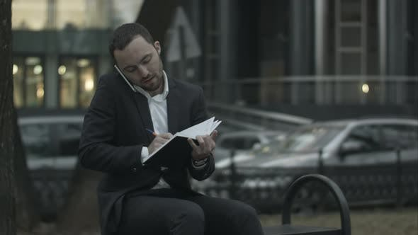 Thumbnail for Young Bearded Businessman Talking By Phone and Writing in Diary, Working with Notes at Green Park.