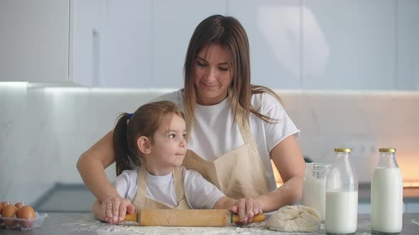 Cover Image for Little Helper Daughter Helps Her Mother Prepare Homemade Dough in the Kitchen