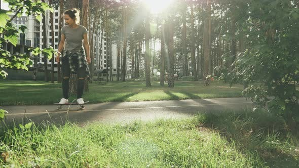 Stylish skater girl skateboarding in park at sunset. Skate lifestyle concept.
