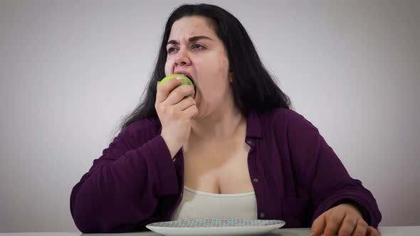 Thumbnail for Portrait of Young Plump Caucasian Woman Taking Apple and Signing. Upset Fat Girl Eating Healthy Food