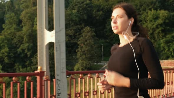 Thumbnail for Woman Jogging on the Bridge During the Sunrise Time. Female Athlete Running Fitness Lifestyle