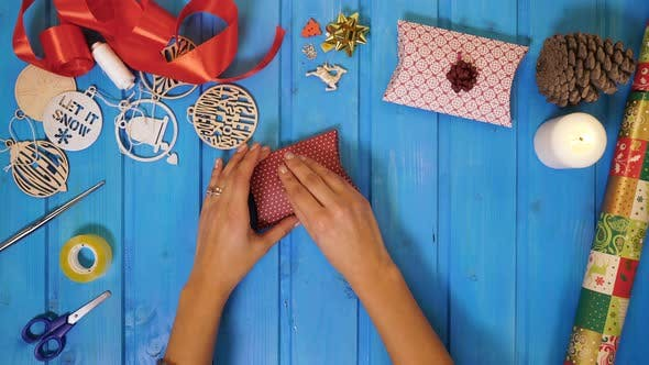 Thumbnail for Hands putting a bow on a gift box