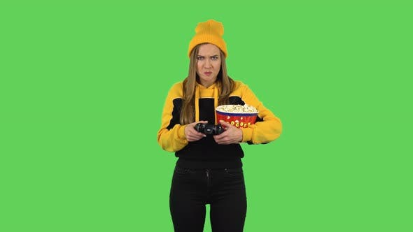 Thumbnail for Modern Girl with Popcorn Is Playing a Video Game Using a Wireless Controller and Rejoicing in
