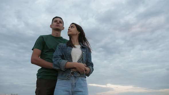 Thumbnail for Cheery Boy Hugging His Girl Standing at the Black Sea Coast at Sunset in Slo-mo