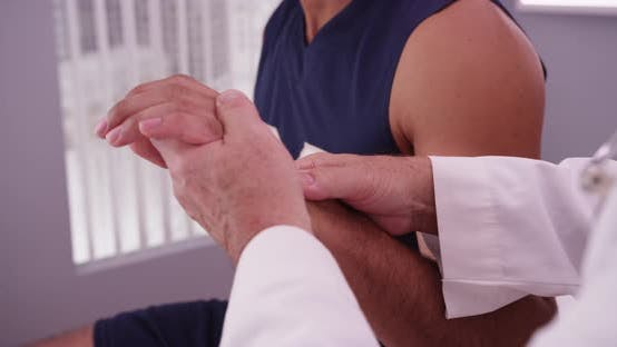 Thumbnail for Mid-aged doctor examining injured wrist of African-american athlete