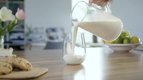 Milch in Glas gießen