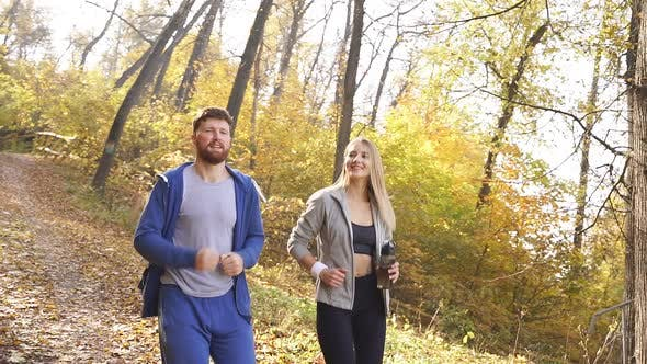 Married Couple Dressed in Sports Clothes Running Around the Park on a Sunny Autumn Day Surrounded By