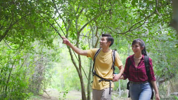 Asian couple are feeling fresh and relax in nature wild, looking and pointing the view in forest