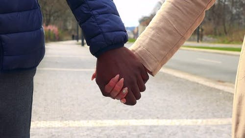 A Black Man and an Asian Woman Grasp Each Other's Hands - Closeup, a Street in the Blurry Background