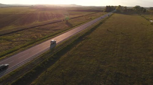 Aerial shot: vehicles, trucks and cars driving by road