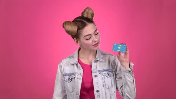 Thumbnail for Teenager wirbt eine Karte und zeigt einen Daumen nach oben. Rosa Hintergrund