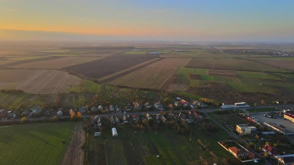 Aerial View of Village Roofs of a House in View of Green Countryside Field