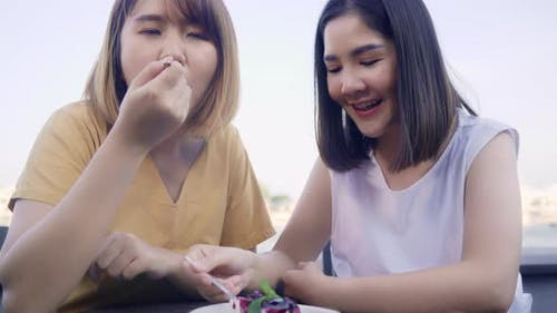 Cheerful young Asian lesbian couple eating food and cake at coffee shop.