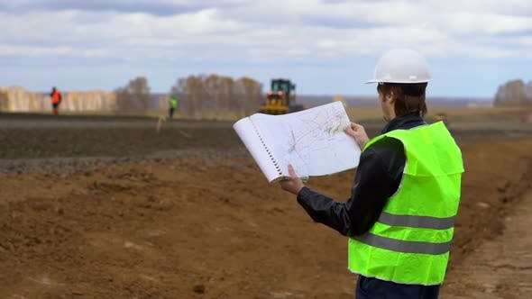 The Worker Looks at the Drawings on the Background of the Road Under Construction