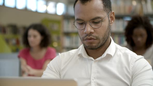 Thumbnail for Closeup Shot of Focused Young Man Using Laptop at Library
