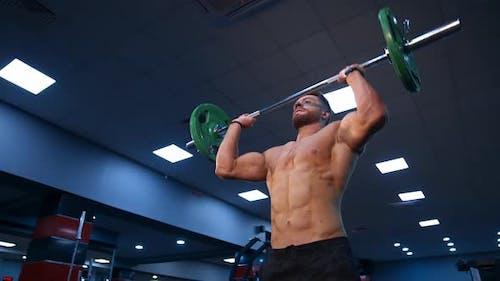 Handsome male bodybuilder lifts barbel over head. Selective focus on shirtless athlete.