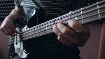 Musician Plays on Bass Guitar in the Studio