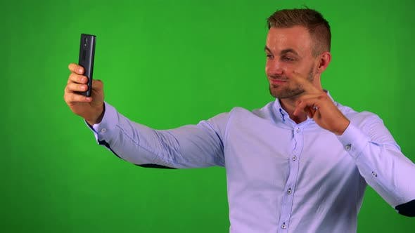 Thumbnail for Young Handsome Business Man Photographs with Smartphone (Selfie) - Green Screen - Studio
