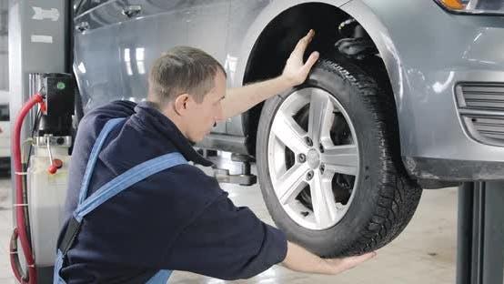 Thumbnail for Car Raised On Lift On Car Service, Mechanic Checks Tires