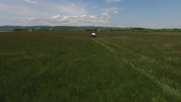 Thumbnail for Aerial shot of tractor spraying grass seed farm