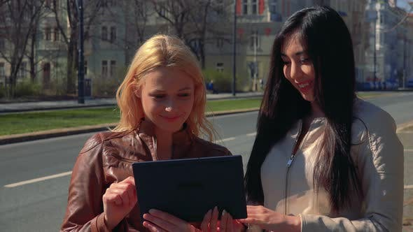 Cover Image for A Young Caucasian Woman Explains Something About a Tablet To a Young Asian Woman - an Urban Area