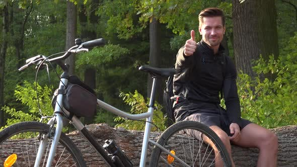 Thumbnail for A Young Handsome Cyclist Sits on a Log Next To His Bike in a Forest and Shows a Thumb Up