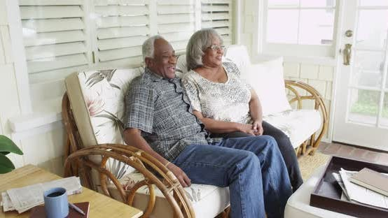 Thumbnail for Senior black couple sitting on couch talking