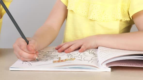 Thumbnail for A Girl Paints a Coloring Book. Close-up of a Little Girl's Hand Holding a Pencil and Drawing.
