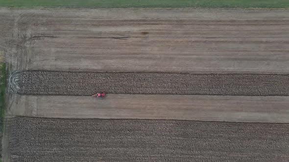 Luftaufnahme des landwirtschaftlichen Feldes Modernes rotes Traktor-Pflügen Land.