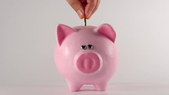 Thumbnail for Male hand throws metal golden coin into a pink piggy moneybox