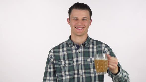 Thumbnail for Handsome Young Man Smiling Joyfully, Holding Out His Beer To the Camera