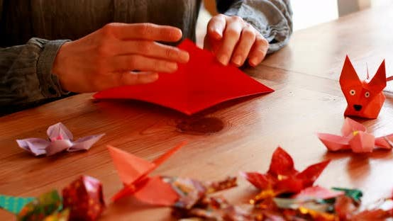 Thumbnail for Woman preparing origami with paper at home 4k