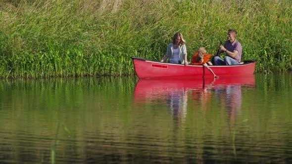 Thumbnail for Family paddling canoe on lake