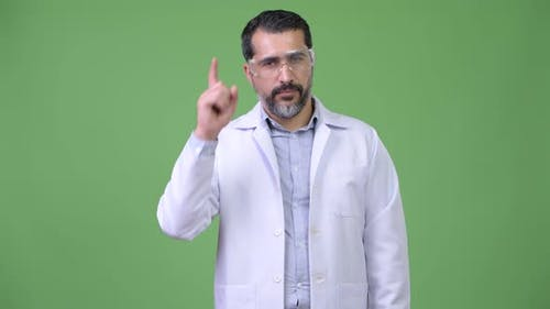 Handsome Persian Bearded Man Doctor Wearing Protective Glasses and Pointing Up