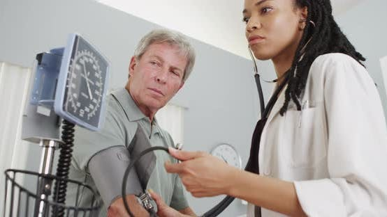 Thumbnail for Black woman doctor checking patient's blood pressure