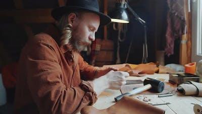 Portrait of Leather Craftsman at Desk in Workshop