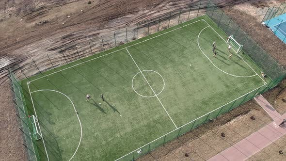 Boys playing soccer, training on football field.