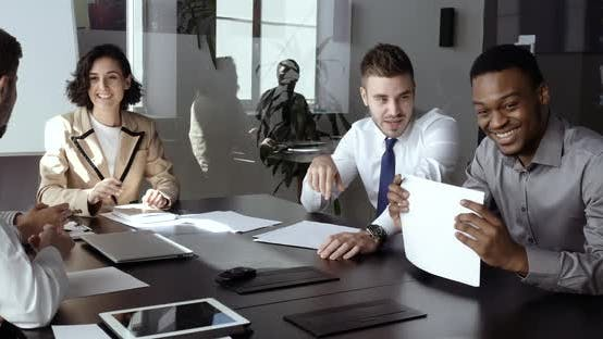 Thumbnail for Group of Smart Multiracial Young Managers Office Workers Sitting at Table in Conference Room