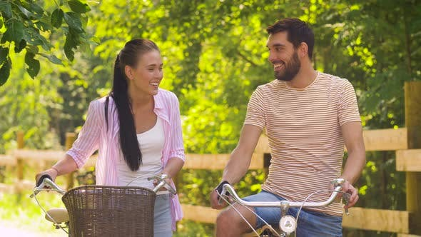 Thumbnail for Happy Couple with Bicycles Talking at Summer Park