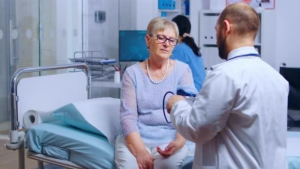 Practitioner Measures Senior Retired Woman Blood Pressure