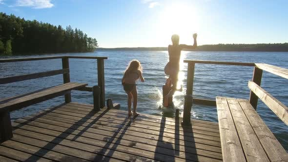 Thumbnail for Family Couple with Daughter Running on a Wooden Pier and Jumping Into the Lake