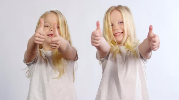 Thumbnail for 6-year-old Twins Posing with Thumbs Up