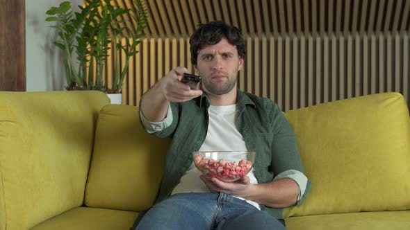 Young Man Sitting on Home Yellow Sofa Watching TV and Eating Popcorn Enjoying Comedy Movie