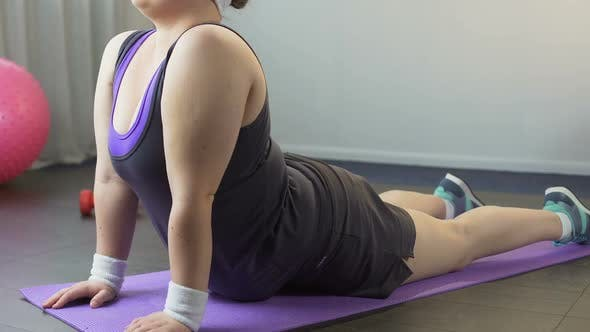 Thumbnail for Plump Girl Skillfully Doing Complex of Stretching and Warming Exercises at Home