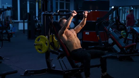 Fit young man lifting barbells doing workout at a gym.