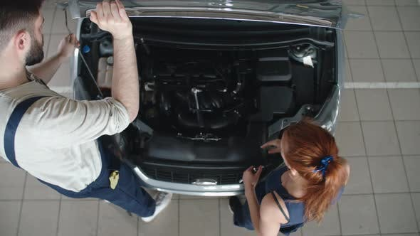 Cover Image for Man and Woman Repairing Car